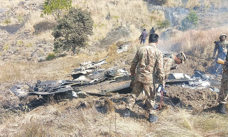 PAKISTANI soldiers stand next to the wreckage of an Indian fighter jet shot down in the Somani area, in Bhimber district near the Line of Control in AJK, on Wednesday. —AFP