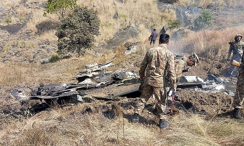Pakistani soldiers stand next to the wreckage of an Indian fighter jet shot down in Azad Jammu and Kashmir at Somani area in Bhimbar district near the Line of Control on February 27, 2019. — AFP