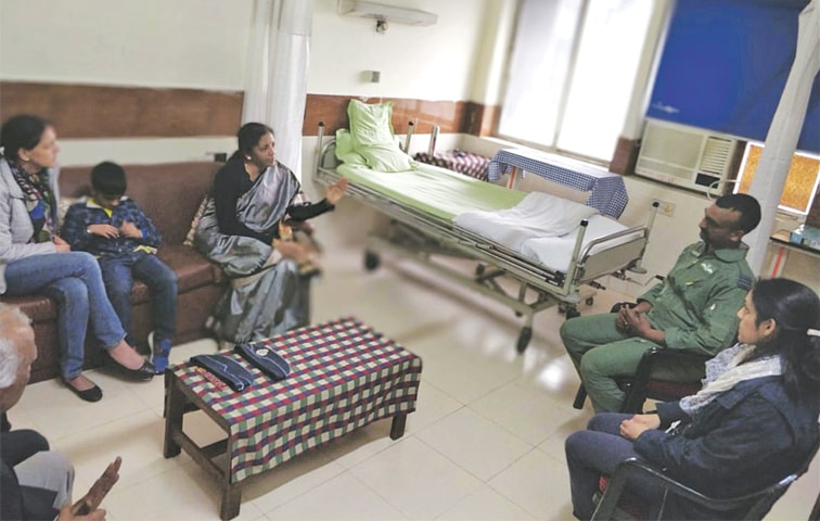NEW DELHI: Indian Defence Minister Nirmala Sitharaman (centre) talking to Wing Commander Abhinandan Varthaman of the Indian Air Force at a hospital on Saturday.—AP