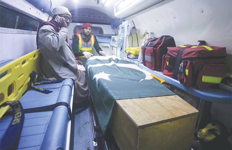 LAHORE: A family member of a Pakistani prisoner, who was killed by Indian inmates in Jaipur jail a few days ago, sits next to his body in an ambulance arriving from India at the Wagah border crossing on Saturday. Shakirullah was killed apparently in retaliation for the Feb 14 suicide bombing in India-held Kashmir that left over 40 soldiers dead.—AP