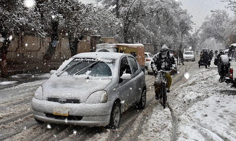 کوئٹہ میں ہونے والی برف باری کے باعث ایک گاڑی کی چھت پر اور سڑک کے اطراف برف دیکھی جا سکتی ہے— فوٹو: اے پی