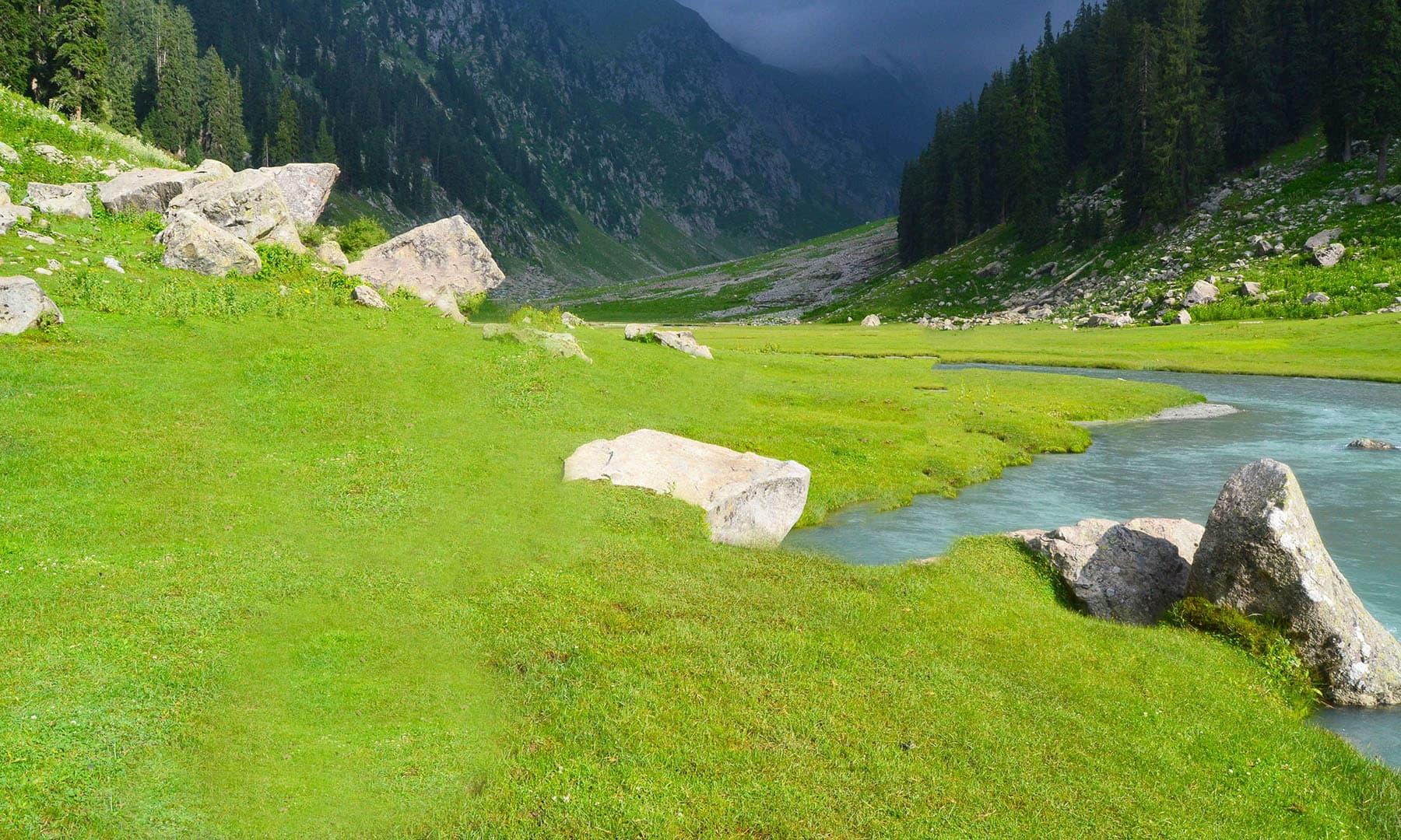 دریا کے پار قالین نما ایک سبزہ زار علاقہ، جو ہماری منزل بھی تھا—عظمت اکبر
