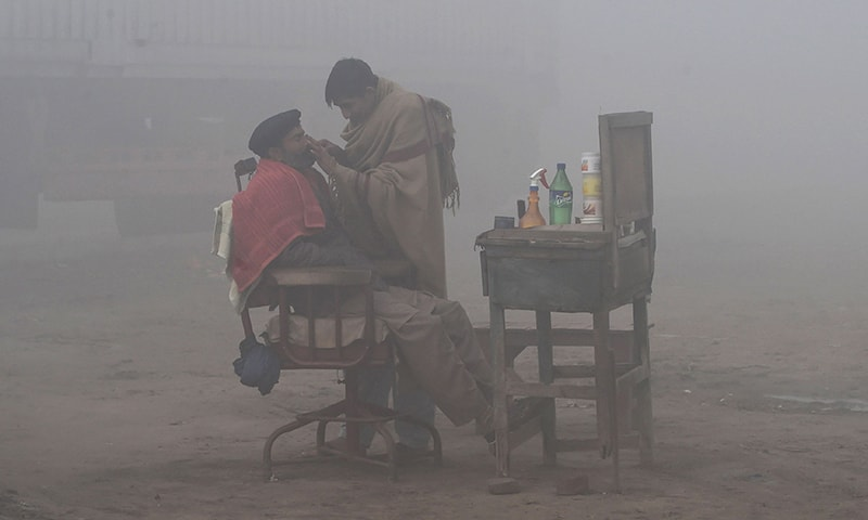 In this file photo taken on January 24, a barber shaves a customer alongside a road amid heavy fog and smog conditions in Lahore. — AFP