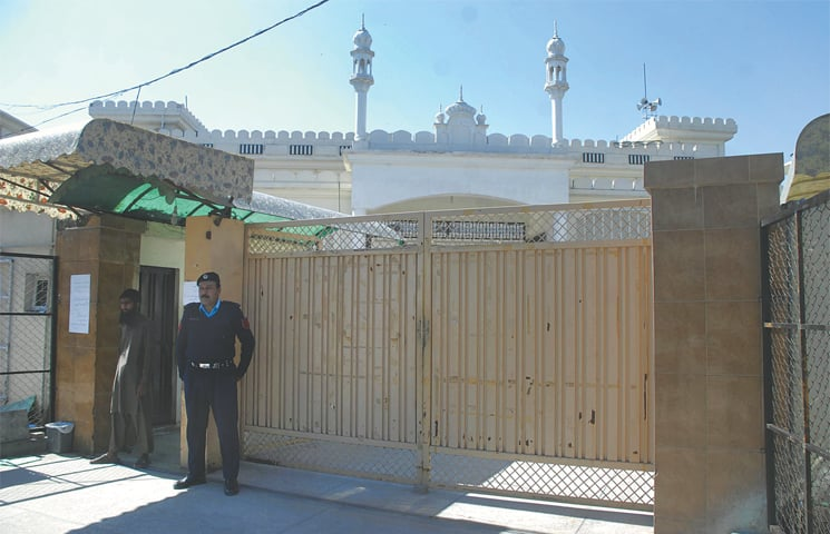 A policeman stands at the entrance of Masjid Quba following directives of the government to take over assets of proscribed organisations.—Tanveer Shahzad / White Star