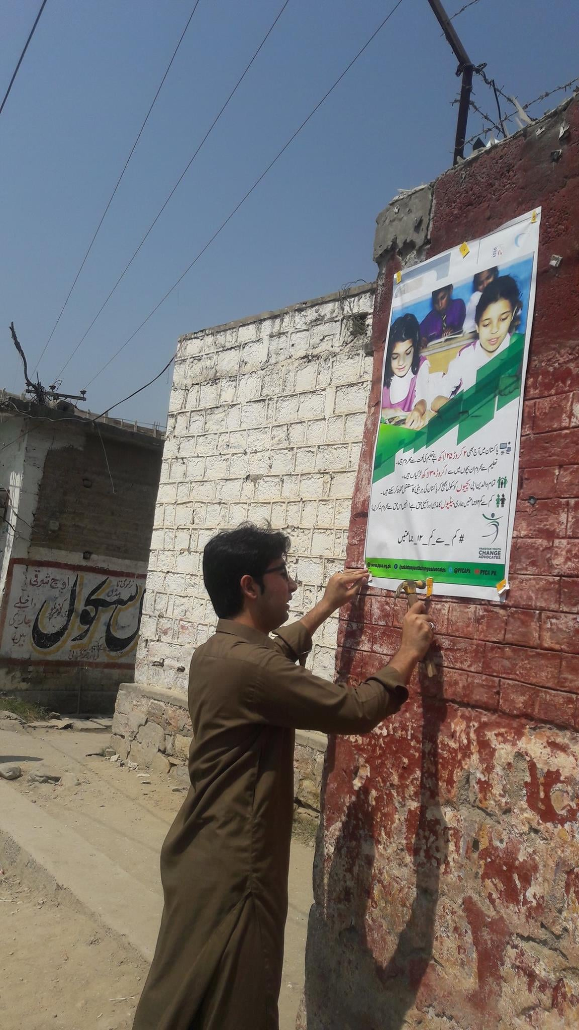 A PYCA volunteer in Lower Dir while placing a banner in his local community