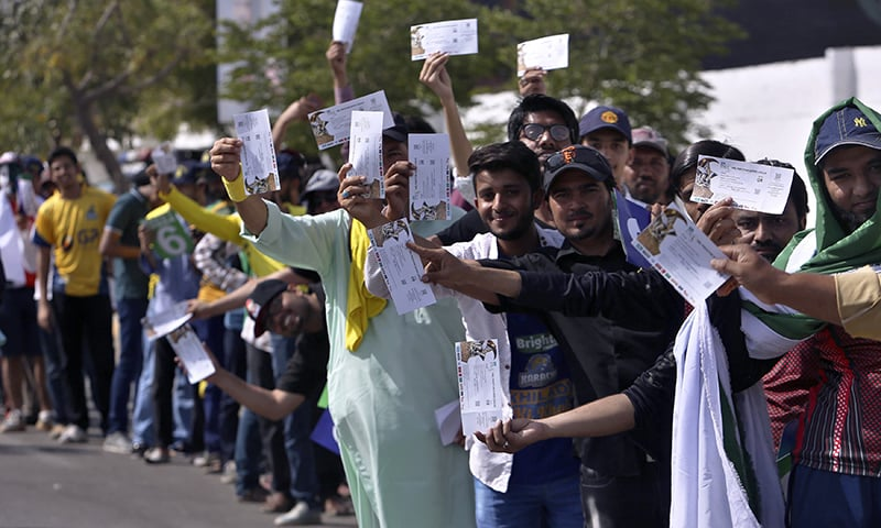 Cricket fans display their tickets while standing in a queue to enter National Stadium for Pakistan Super League final cricket match in Karachi, Pakistan, Sunday, March 25, 2018. — AP