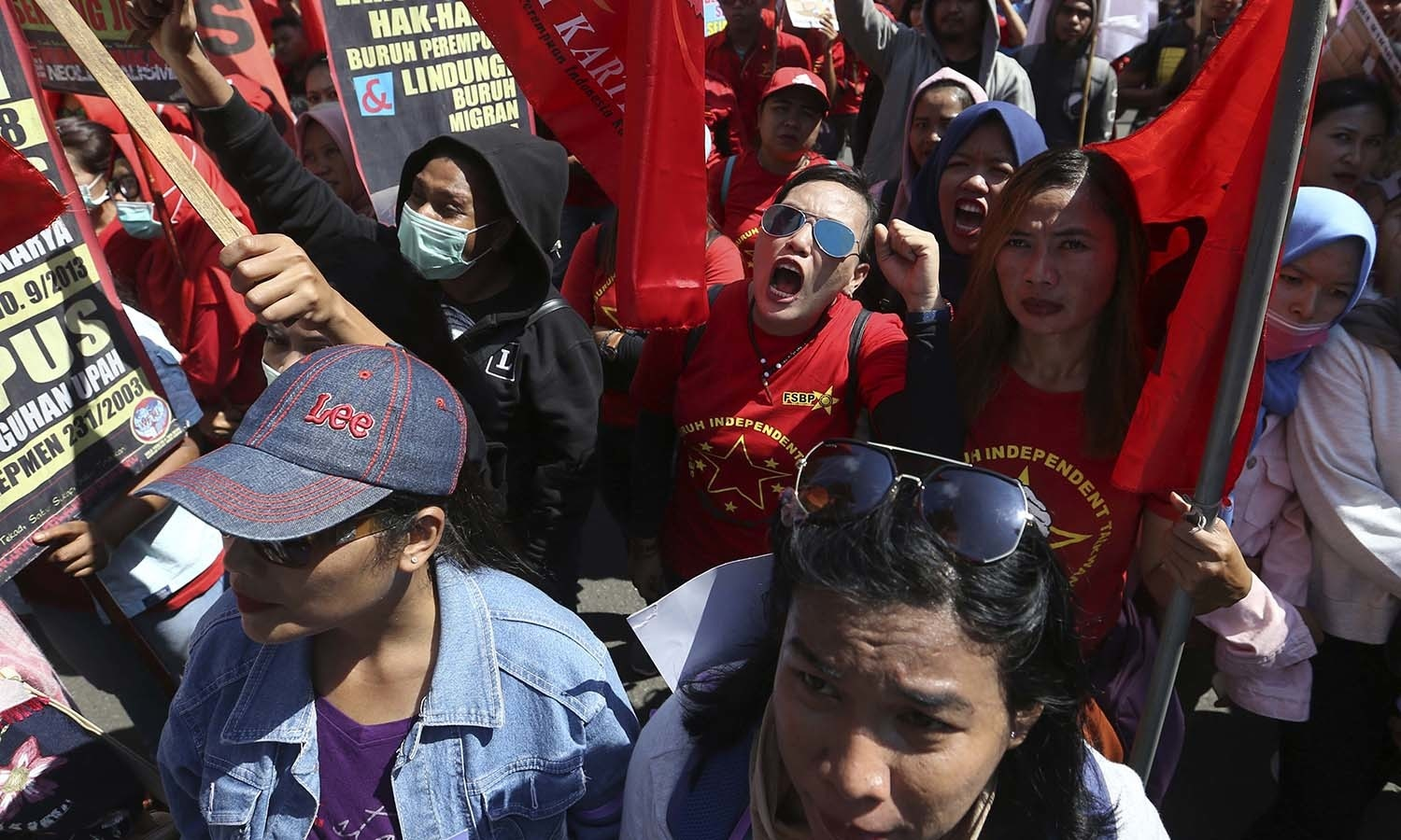 Women activists shout slogans as they mark International Women's Day during in Jakarta, Indonesia. — AP
