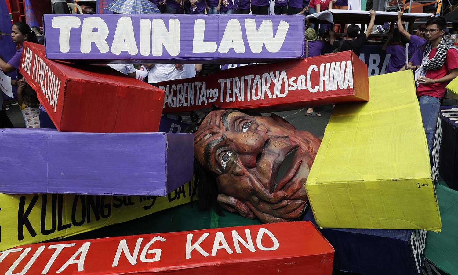 An effigy of Philippine President Rodrigo Duterte lies under coloured paper blocks as women groups mark International Women's Day during a rally near the Malacanang presidential palace in Manila, Philippines. — AP