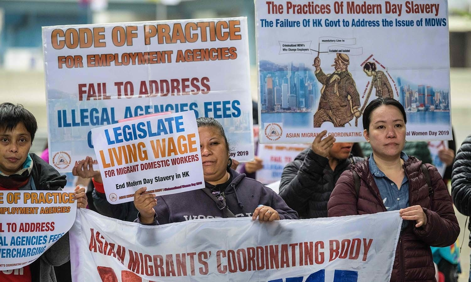 Migrant domestic helpers and activists hold placards as they attend a protest demanding better working conditions to mark International Women's Day in Hong Kong. — AFP
