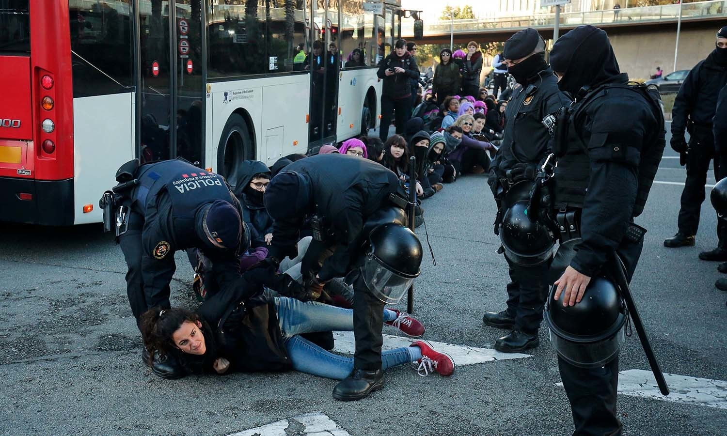 Catalan regional police forces Mossos d'Esquadra drag a woman as they disperse demonstrators blocking the Gran Via street during a protest marking International Women's Day in Barcelona. — AFP