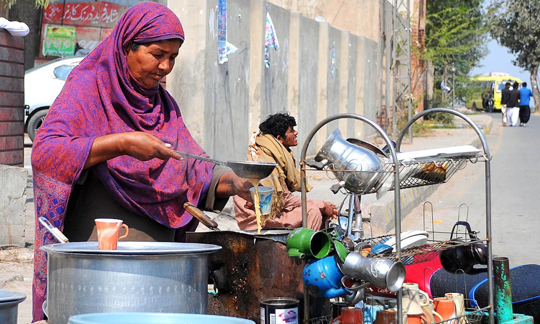 A female vendor prepares tea at her pushcart in Multan as International Women's Day is observed on Friday. — APP