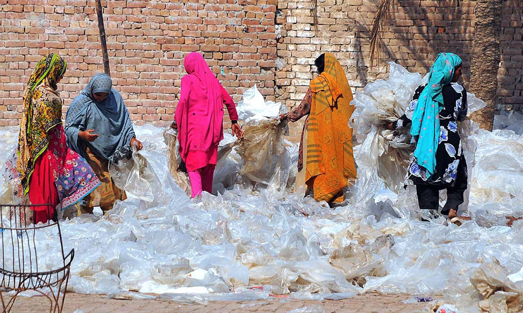 Lady workers spread plastic bags for drying purposes at a local factory in Multan on International Women's Day. — APP
