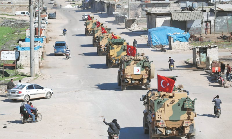 SARAQIB: A column of Turkish military vehicles drives along a road in the demilitarised zone in Syria's Idlib province.—AFP