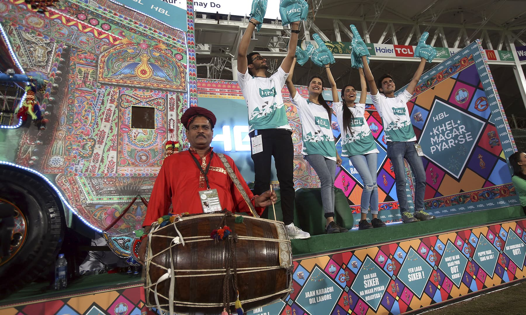 Cricket fans dance on traditional drum beat. — AP