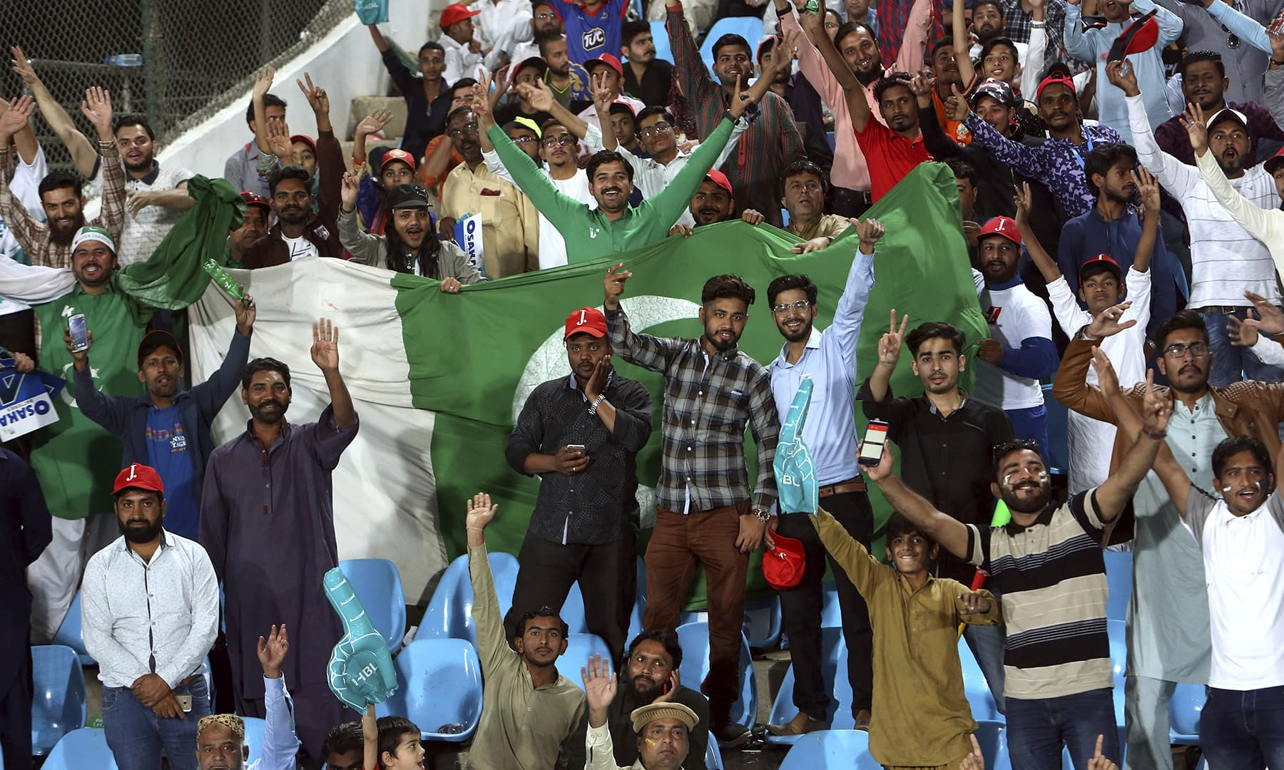 Spectators cheering and waving the Pakistan flag proudly. — AP