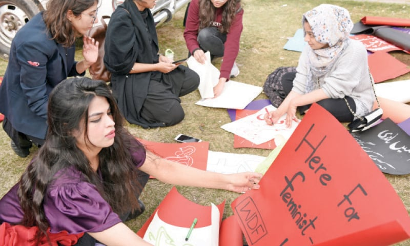 Young women work on their placards in preparation for the march.