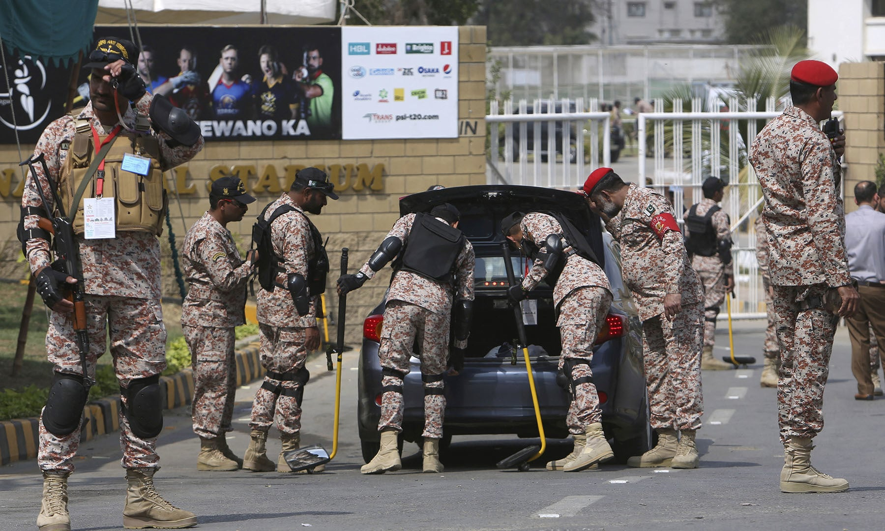 A paramilitary soldier stands guard while others search a car at the main entrance to National Stadium ahead of the PSL match in Karachi on Saturday. — AP