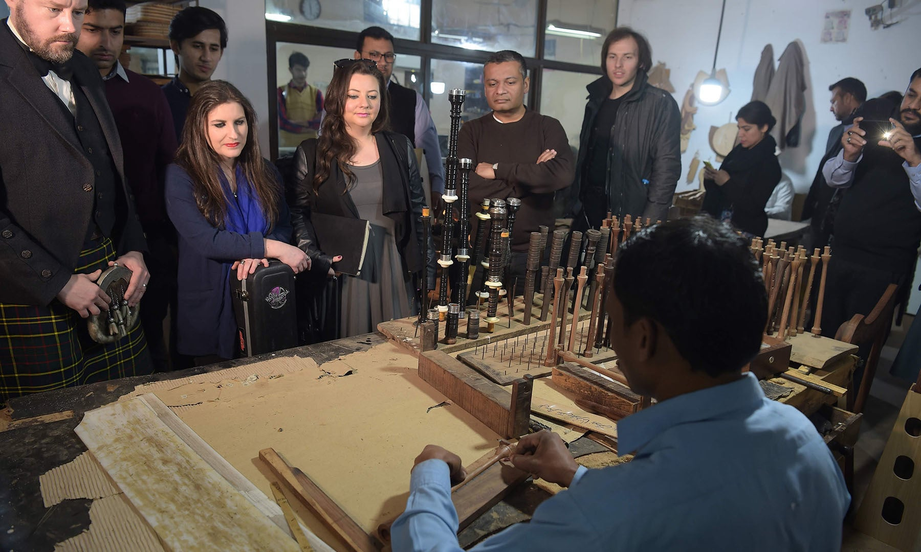 In this picture taken on January 25, visiting international musicians watch the process to make bagpipes at the Mid East bagpipe factory in Sialkot.  — AFP