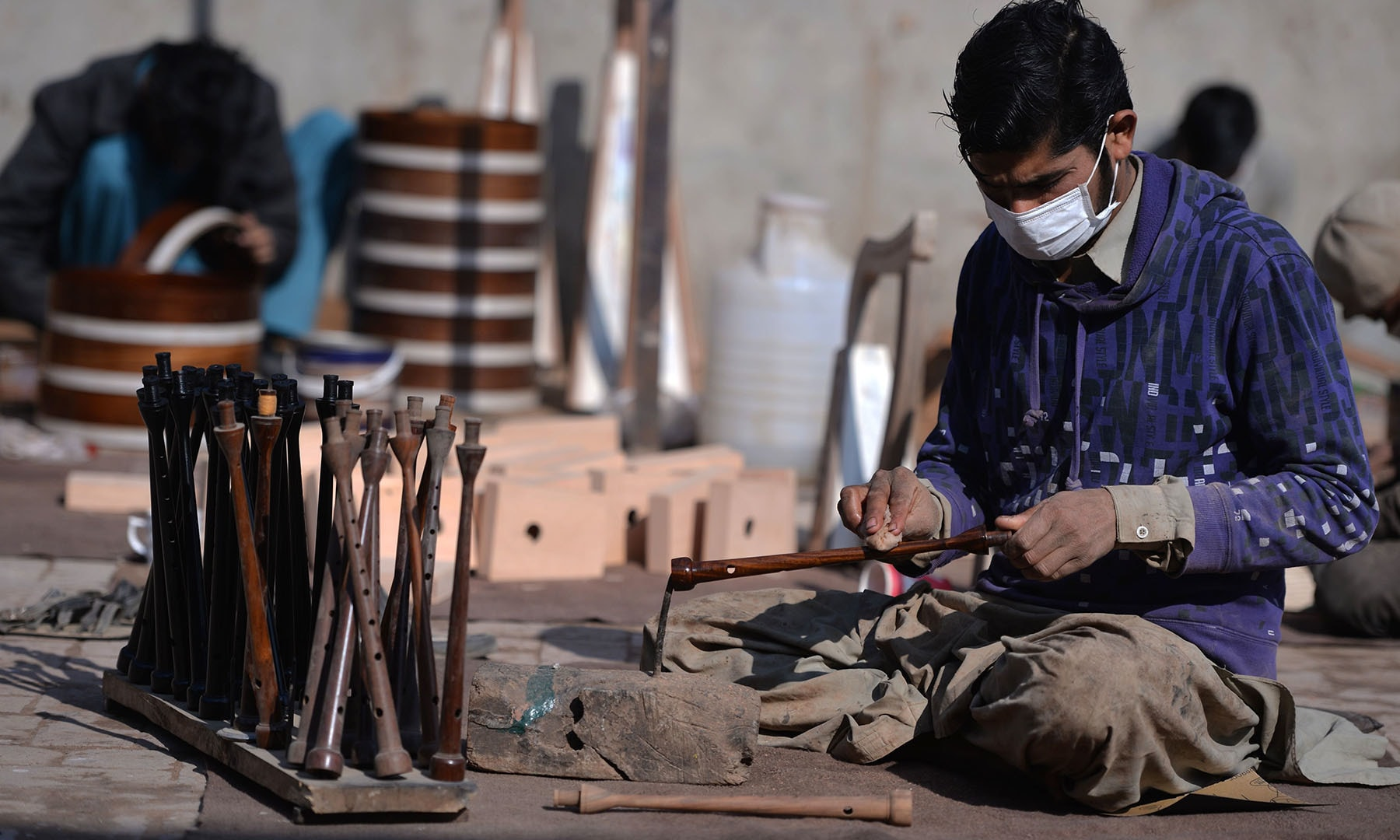 In this picture taken on January 25, a worker polishes a component to be used to make a set of bagpipes at the Mid East bagpipe factory in Sialkot. — AFP