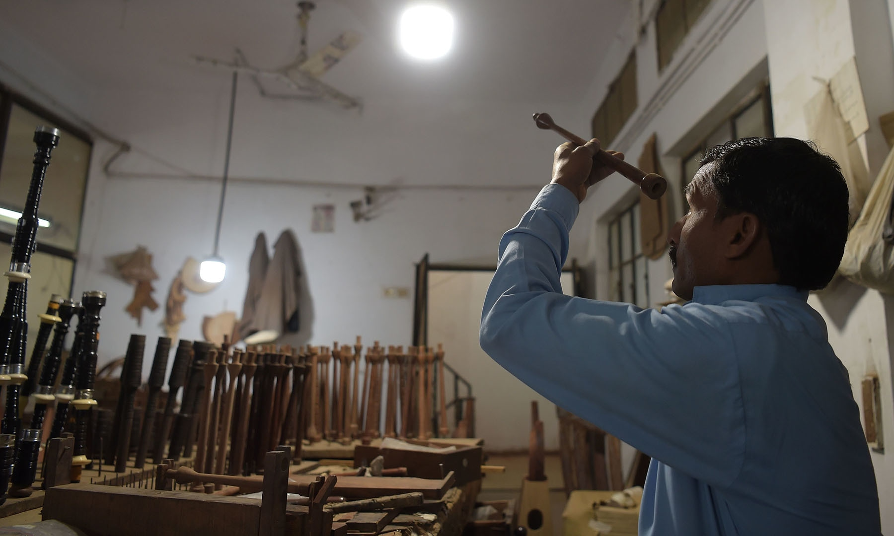 In this picture taken on January 25, a worker prepares a component to make a set of bagpipes at the Mid East bagpipe factory in Sialkot.  — AFP