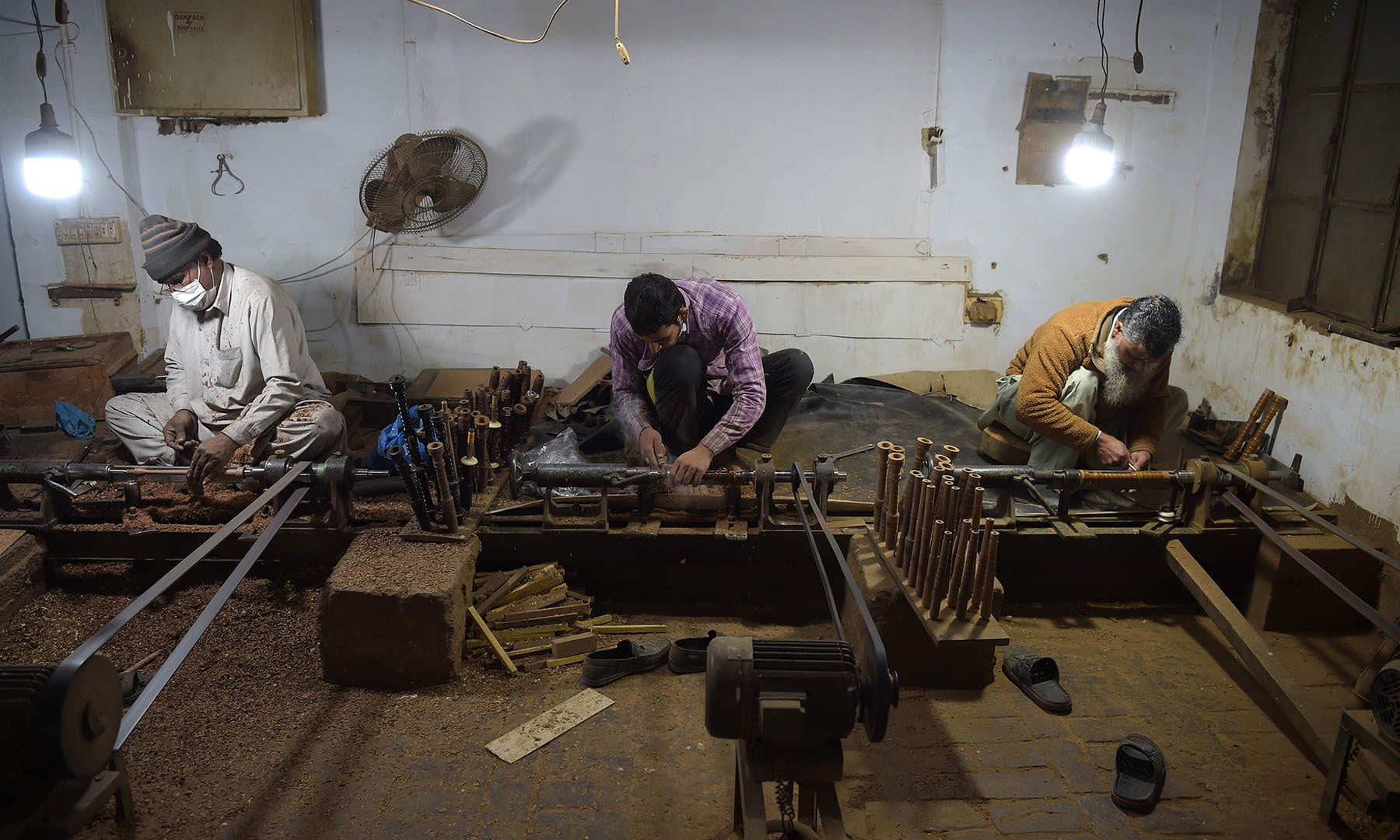 In this picture taken on January 25, artisans work on machines to make components to be used in bagpipes at the Mid East bagpipe factory in Sialkot. — AFP
