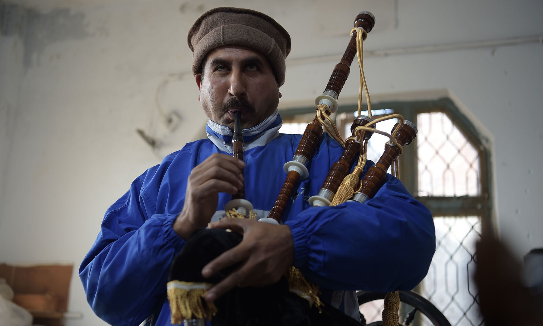 In this picture taken on January 25, a worker plays and tests a set of bagpipes at the Mid East bagpipe factory in  Sialkot.  — AFP