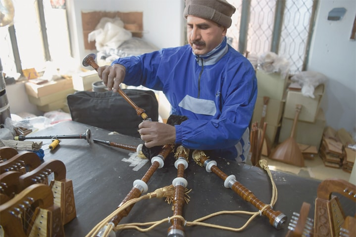 Sialkot: In this Jan 25 picture, a worker fixes a component to make a set of bagpipes at a bagpipe factory.—AFP