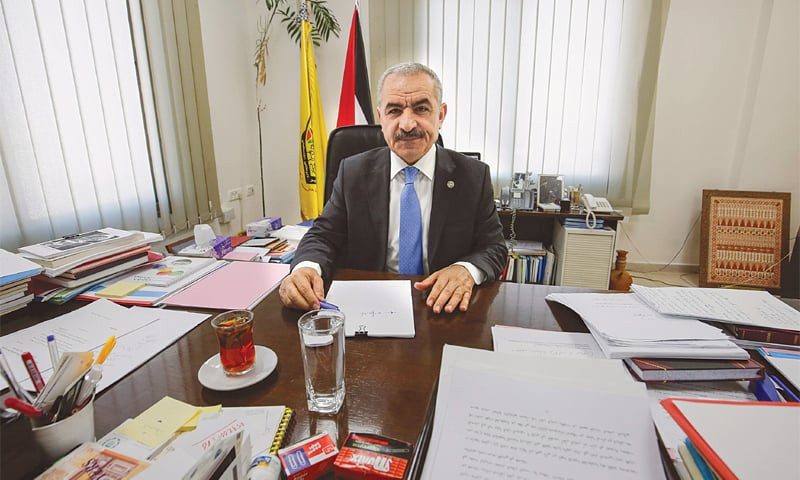 Ramallah: Newly-appointed Palestinian Prime Minister Mohammad Shtayyeh sits behind his desk at his office on Sunday. —AFP