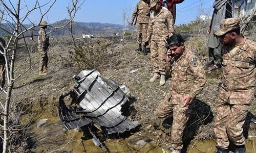 Pakistani soldiers stand next to the wreckage of an Indian fighter jet shot down on February 27, 2019, in Bhimbar district near the Line of Control. — ISPR/File