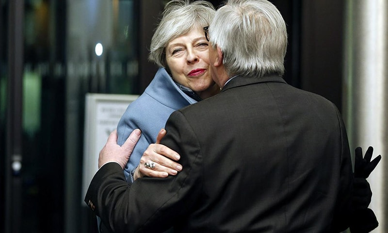 British Prime Minister Theresa May, background, is welcomed by European Commission President Jean-Claude Juncker in Strasbourg, France.—AP