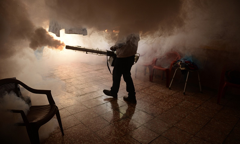 A photo of a person fumigating a facility. — AFP/File