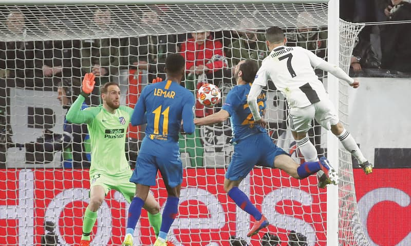 TURIN: Juventus' Cristiano Ronaldo (R) scores during the second leg of their Champions League round-of-16 tie against Atletico Madrid at the Allianz Stadium.—AP