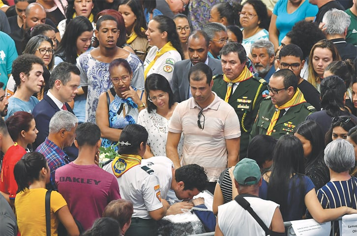 SAO PAULO: Relatives and friends of victims of the school shooting pay their respects during a collective wake on Thursday.—AFP
