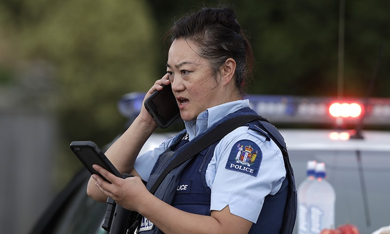 A police officer talks on her phone as a roadblock near a mass shooting at a mosque in Linwood, Christchurch, New Zealand. — AP