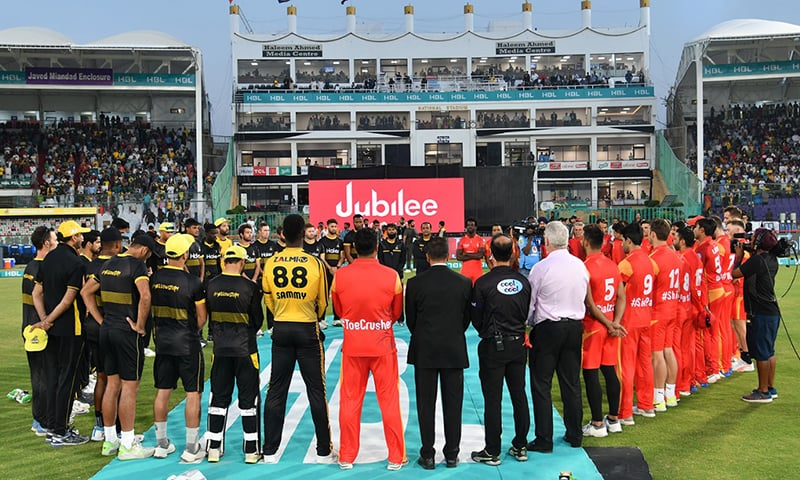 Players and match officials gather around to observe a minute of silence for the victims of the terror attack in New Zealand on March 15, 2019. — PCB