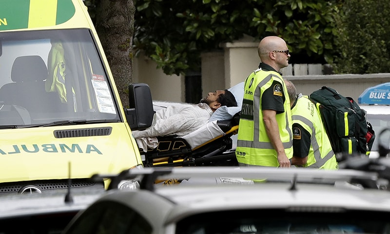 Ambulance staff take a man from outside a mosque in central Christchurch. — AP