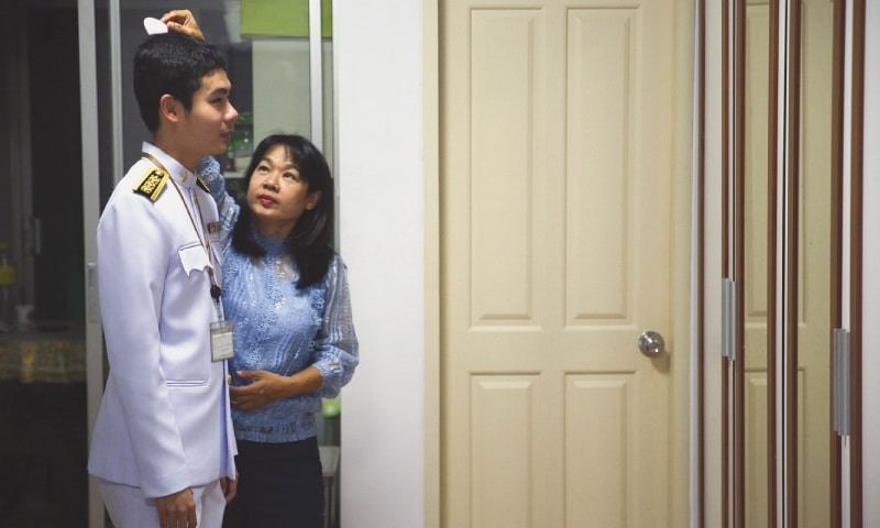 Bangkok: Damkerng Mungthanya, a blind teacher, is being combed by his mother  at his apartment.—Reuters