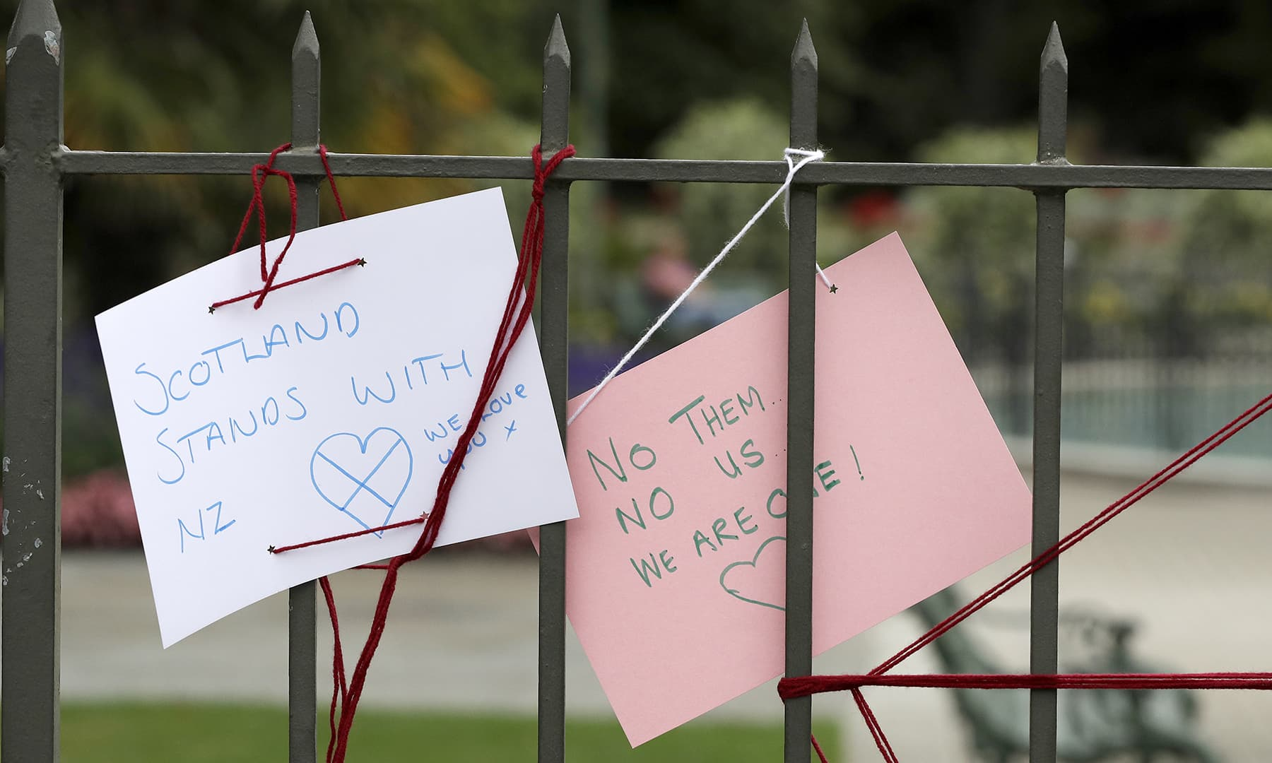 Signs are tied to a wall at the Botanical Gardens Saturday, March 16, 2019, in Christchurch, New Zealand. — AP