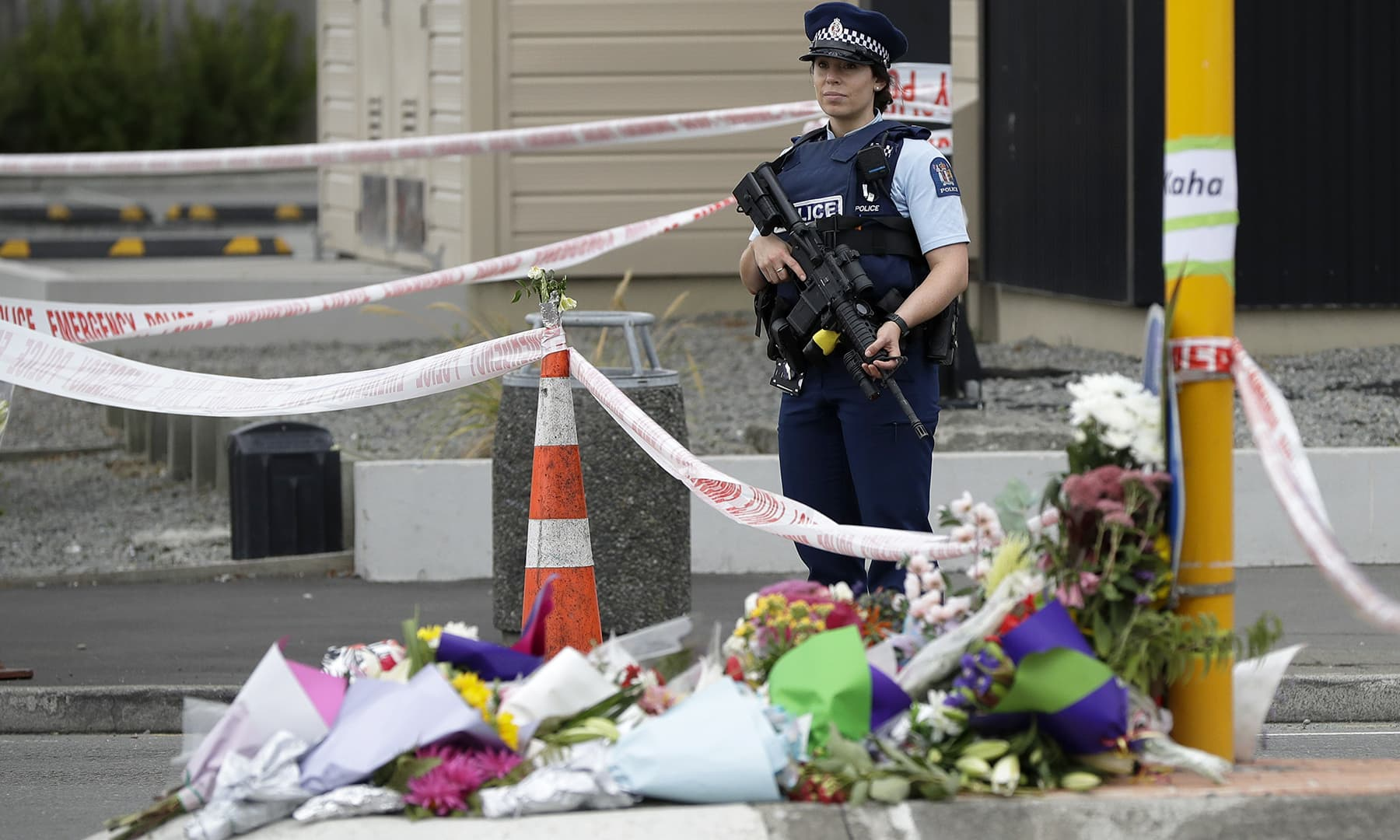 Police stand by a collection of flowers near the Linwood Mosque in Christchurch, New Zealand, Saturday, March 16, 2019. — AP