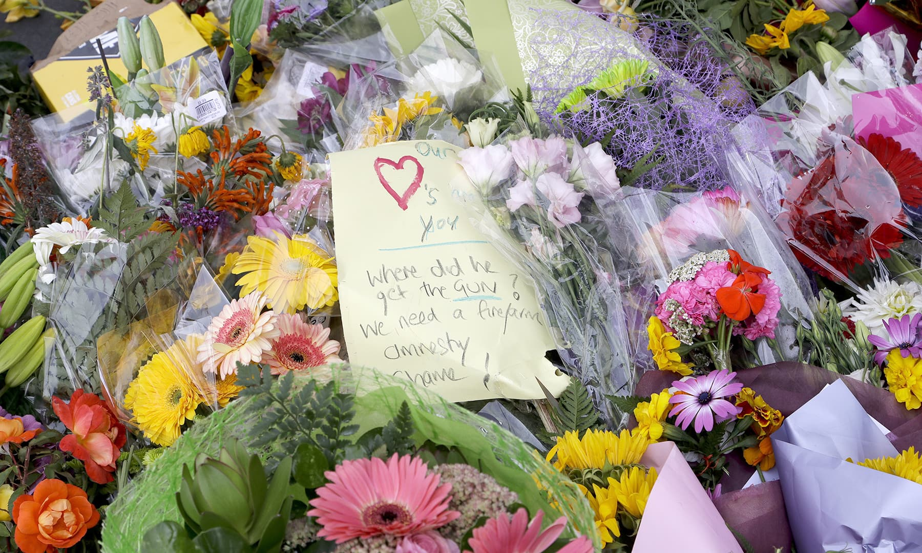 A handwritten message is placed at a collection of flowers left near the Masjid Al Noor mosque in Christchurch, New Zealand, Saturday, March 16, 2019. — AP