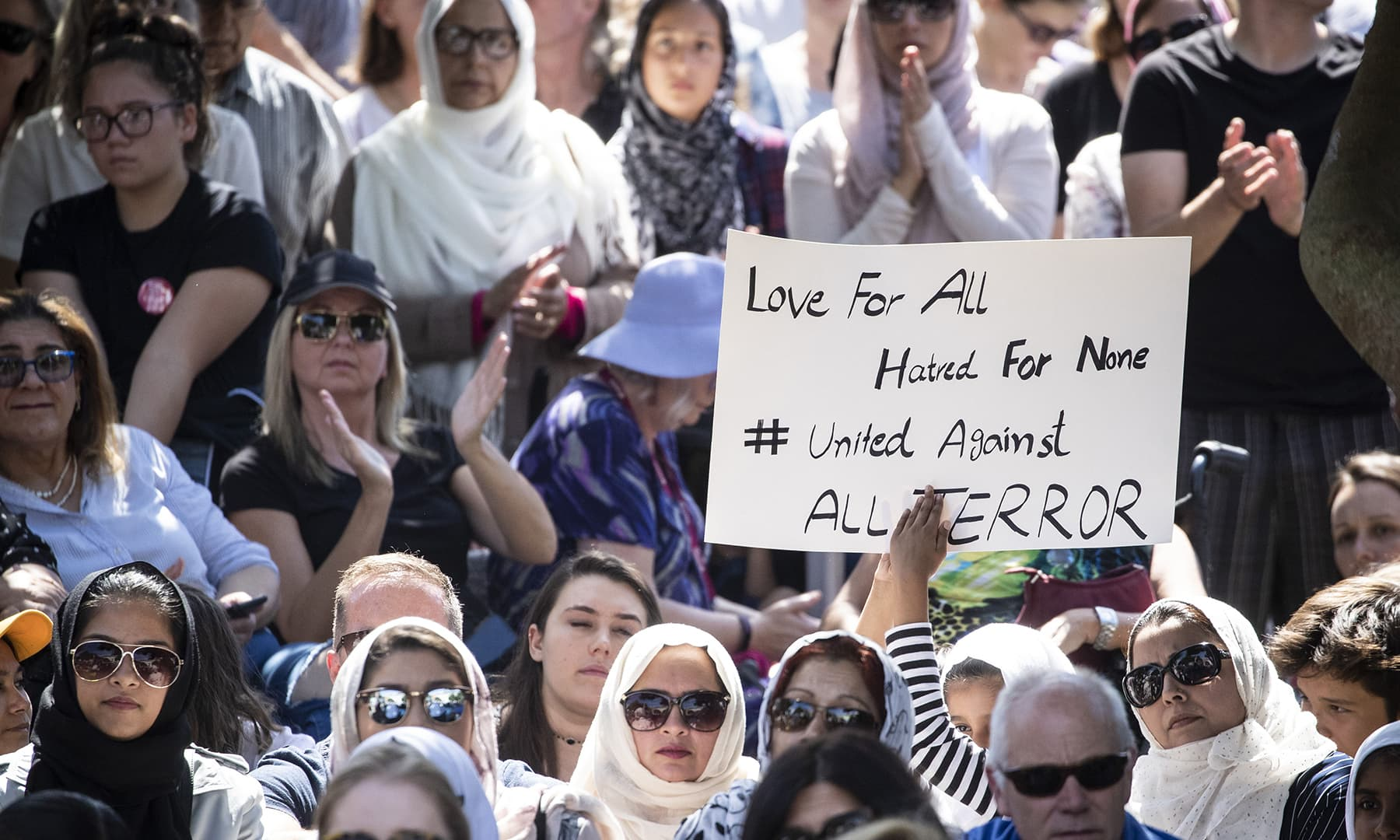 People hold up signs of support at a vigil in Aotea Square in support of the victims of the Christchurch mosque killings in Auckland, New Zealand, Saturday, March 16, 2019.