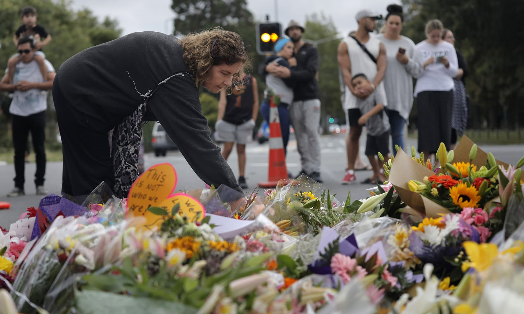 A woman paying her respects to the victims of the attack at a makeshift memorial near the Masjid Al Noor mosque, Saturday, March 16, 2019, Christchurch, New Zealand. —AP