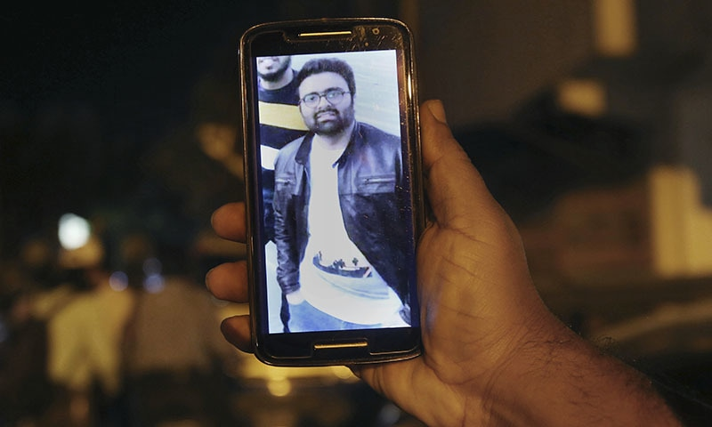 A relative shows the picture of Syed Areeb Ahmed on his cell phone outside his home in Karachi on Saturday. — AP