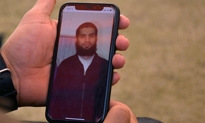 In this picture taken on March 16, a relative looks at a picture on a mobile phone of Talha Naeem in Abbottabad. — AFP