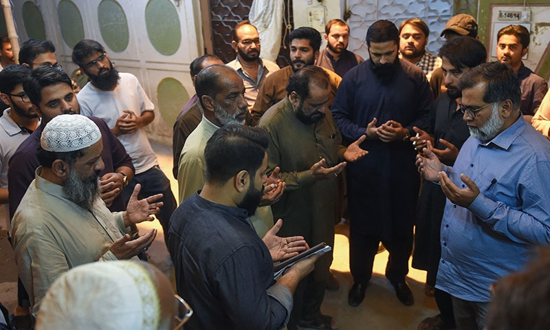 Father of Syed Areeb Ahmed (C), who died in the terrorist attacks on two mosques in New Zealand massacre, is surrounded by people praying for victims in Karachi on March 16, 2019. — AFP