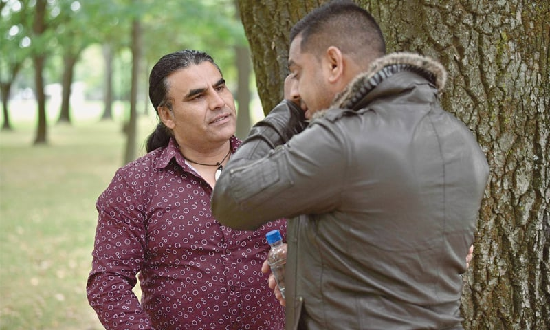 AFGHAN refugee Abdul Aziz (left) talking to a man who met him on Sunday to thank him for his bravery.—AFP