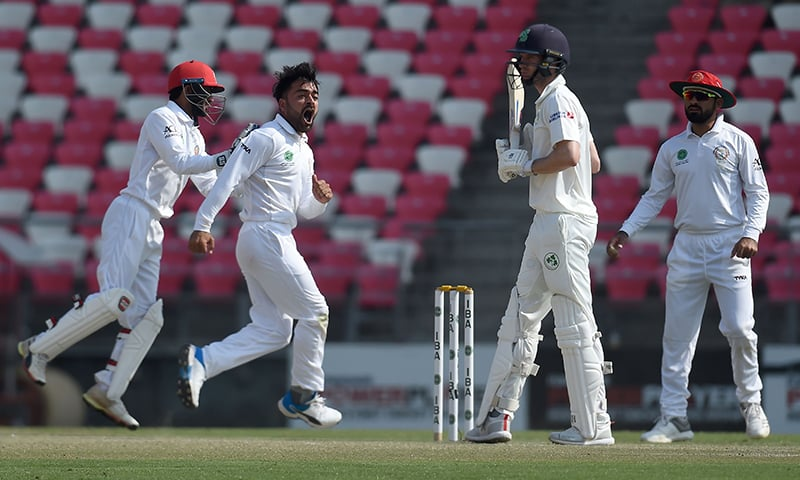 Afghanistan's Rashid Khan (2L) celebrates after dismissing Ireland's George Dockrell (2R) during the third day of the Test cricket match between Afghanistan and Ireland at the Rajiv Gandhi International Cricket Stadium in the northern Indian city of Dehradun on March 17, 2019. — AFP