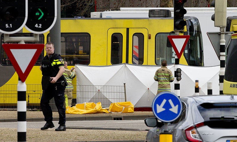 Rescue workers install a screen on the spot where a body was covered with a white blanket following a shooting in Utrecht, Netherlands on Monday. — AP