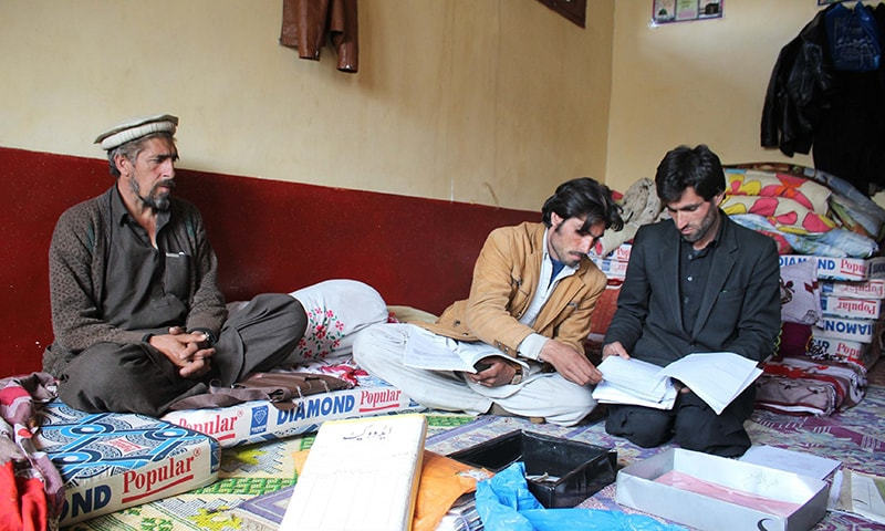 Bin Yasir and Gul Nazar (R) check files of the cases their slain brother Afzal Kohistani had preserved during the long trial of the Kohistan video scandal case. — Photo by author
