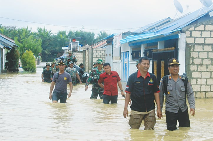 Sentani (Papua province, Indonesia): Police and soldiers search for residents in need of assistance in a flooded neighbourhood. —AP